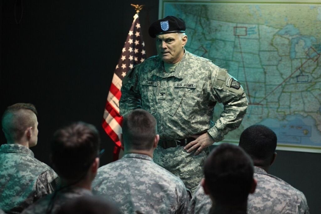 Colonel Crane (Marshall Teague) briefs his troops on controversial action which will pit soldiers versus citizens